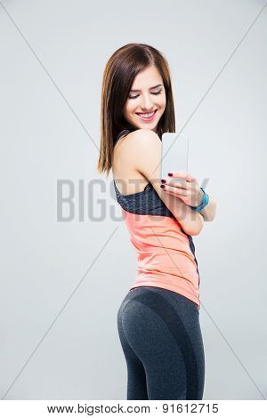 Smiling woman making photo on smartphone over gray background
