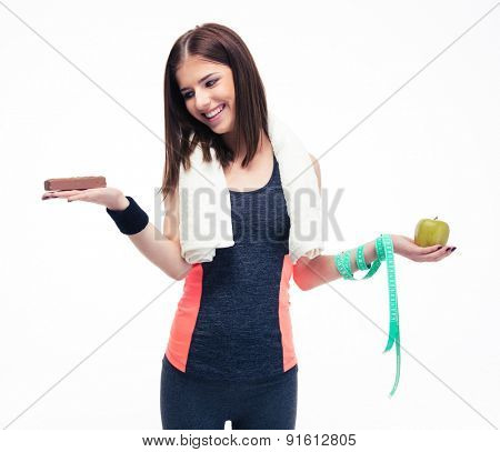 Smiling woman making choice between bananas and chocolate isolated on a white background