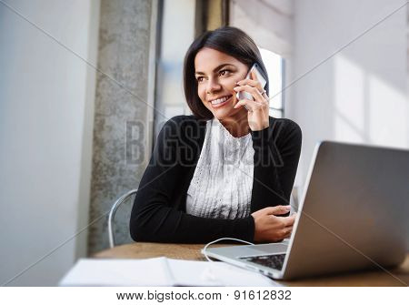 Young happy businesswoman talking on phone in the office