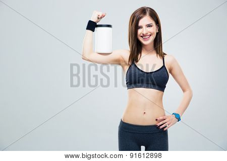 Smiling sporty woman with jar of protein on hand over gray background and looking at camera