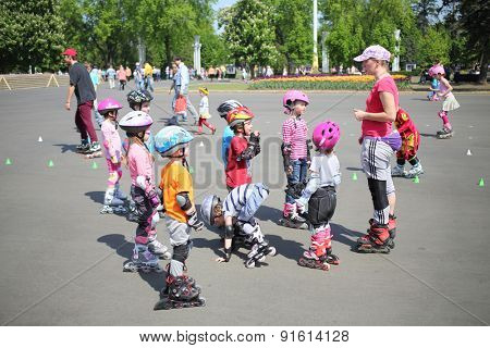 MOSCOW - MAY 18, 2014: A group of children on roller skates and helmet attentively listen to the instructor in the park ENEA