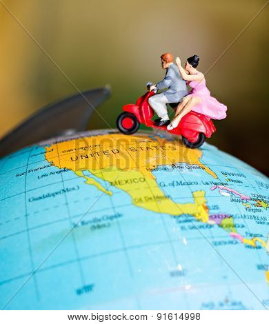 Toy Miniature Figures Of A Couple Traveling On A Vespa