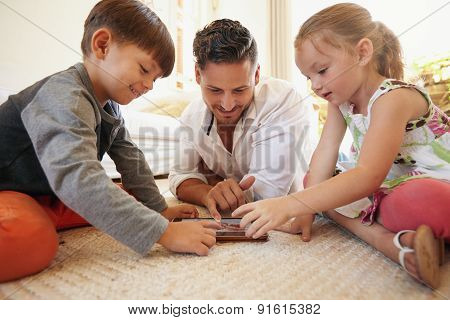 Father And Children Spending Time Together Using Digital Tablet