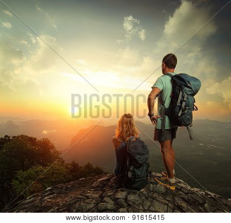 Tourists With Backpacks Enjoying Sunrise On Top Of A Mountain