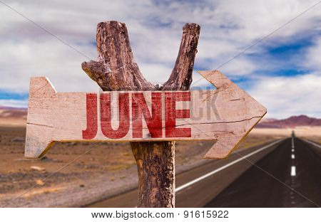 June wooden sign with desert road background