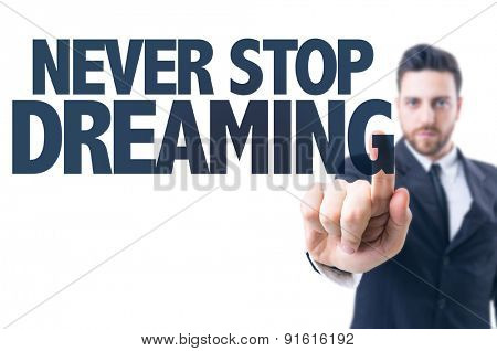 Business man pointing the text: Never Stop Dreaming