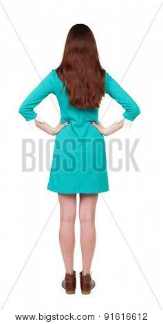 back view of standing young beautiful  woman.  girl  watching. Rear view people collection.   Isolated over white background. The girl in a blue dress with brown boots standing with hands on waist.