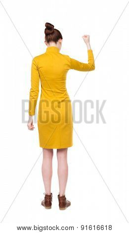 Back view of  woman.  Raised his fist up in victory sign.  Rear view people collection.  backside view of person.  Isolated over white background. Girl in mustard strict dress showing gesture