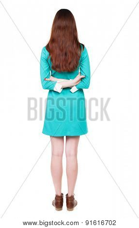 back view of standing young beautiful  woman. Rear view people collection.  Isolated over white background. The girl in a blue dress with brown shoes is hand clasping his hand behind his back.