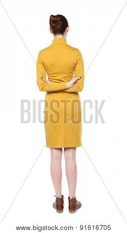 back view of standing young beautiful  woman.  girl  watching. Rear view people collection.  backside view of person.  Girl in mustard strict dress standing with his hands crossed behind his back.