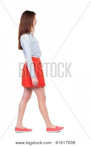side view of walking  woman in red. beautiful blonde girl in motion.  backside view of person.  Rear view people collection.  A woman in a red skirt is left with a smile and looking forward.