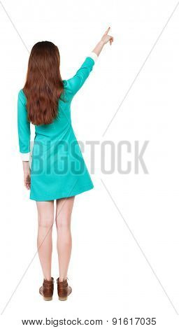 Back view of  pointing woman. beautiful girl. Rear view people collection.  backside view of person.  Isolated over white background. The girl in a blue dress with brown shoes shows the sky.