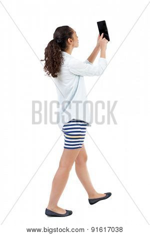 a side view of a woman walking with a tablet PC is in the hands of beautiful curly girl in motion.  backside view of person.  African-American is photographing tablet.
