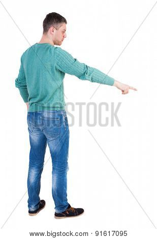 Back view of  pointing young men in jeans. Young guy  gesture. Rear view people collection.   Isolated over white background. The guy in the green jacket stands sideways and shows a finger down right