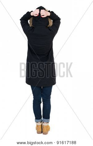 Back view of shocked woman in parka. upset young girl. Rear view people collection.  .  Isolated over white background. Girl in a black winter jacket with a hood terrified her head in her hands.