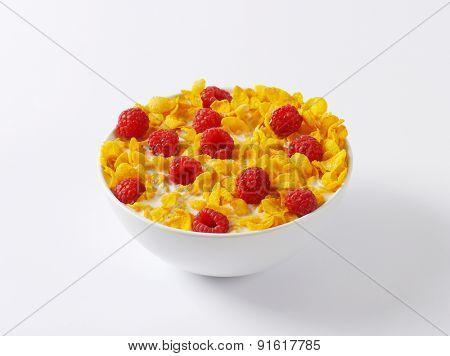 healthy breakfast - bowl of cornflakes and raspberries in milk
