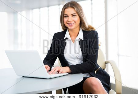 Portrait of a young businesswoman using laptop at office