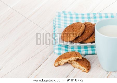 Cup of milk and gingerbread cookies on white wooden table with copy space