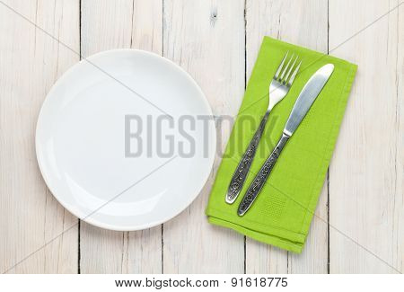 Empty plate and silverware over white wooden table background. View from above