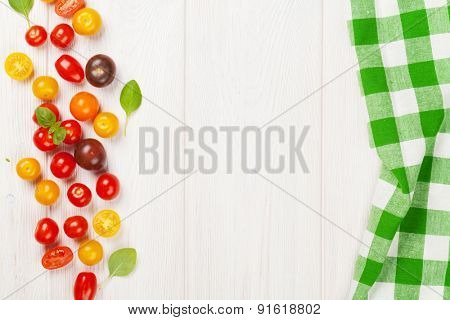 Colorful cherry tomatoes and basil on wooden table background. Top view with copy space
