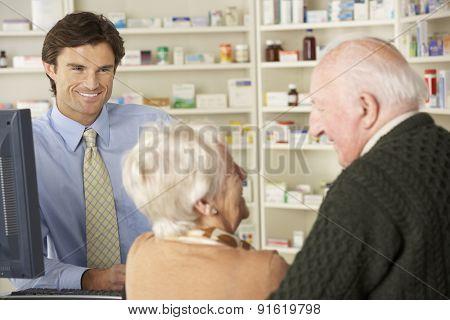 Pharmacist in pharmacy with senior couple