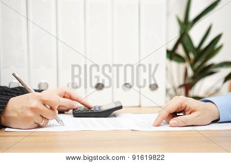 Businessman And Businesswoman Are Analyzing Financial Numbers On Document