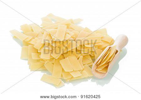 Italian uncooked pasta with wooden scoop