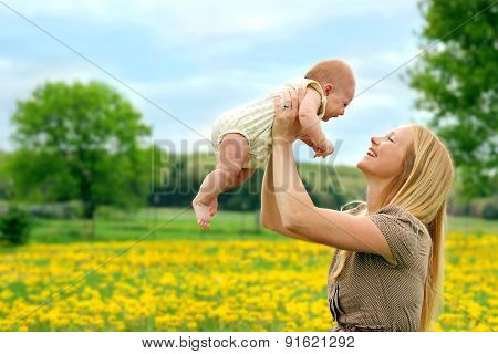 Happy Mother And Newborn Baby Girl Playing Outside