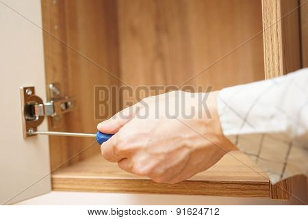 Carpenter Installing  Furniture Door Hinge And Using Screwdriver.