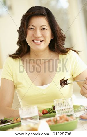 Asian woman eating meal at home