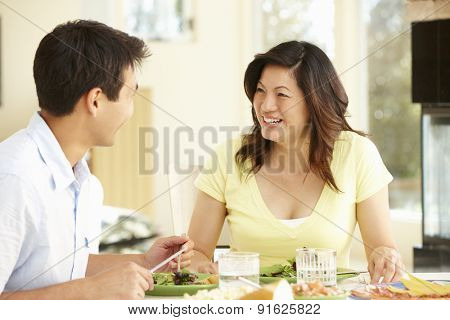 Asian couple sharing meal at home