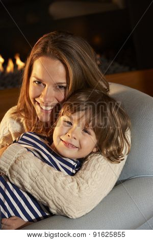 Portrait mother and son sitting in front of fire