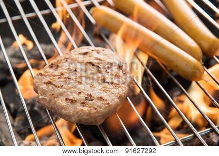 Hamburgers And Sausages Cooking Over Flames On Grill.