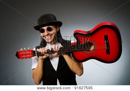 Man wearing sunglasses and playing guitar