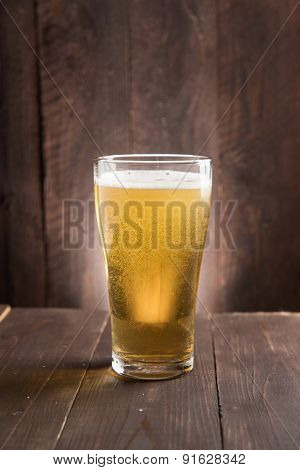 Glass Of Light Beer On Wooden Background.
