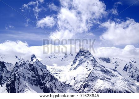 Snowy Mountains In Clouds At Sun Day