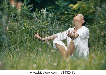 Beautiful Young Woman Meditating On Field. Outdoor, Outside