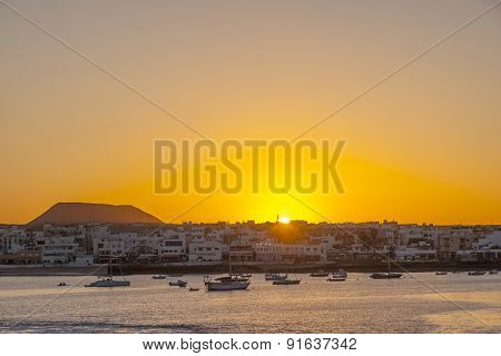 Sunset In The Harbor  With Sailing Boats