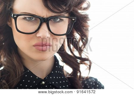 Close Up Of Frown Young Woman Over White Background. Unhappy Girl With Eyeglasses