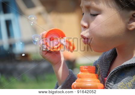 Child Making The Soap Bubbles