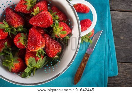 Fresh Strawberries In Rustic Colander On Wooden Table