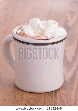 Hot chocolate with cream topping in an antique cup on rustic wooden table