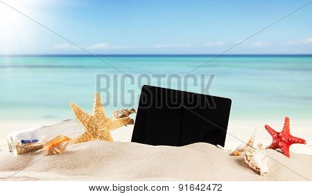 Concept with summer beach, tablet and accessories, blur sea on background