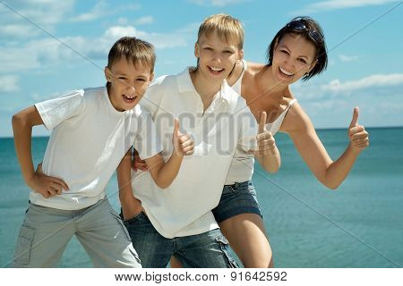 Happy family of four showing thumbs up
