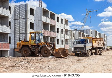 Construction Technics Stands Near A Residential Building Under Construction