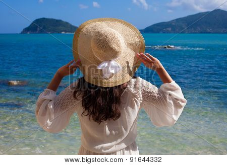 Young woman in summer dress with  straw hat looking to a sky and sea