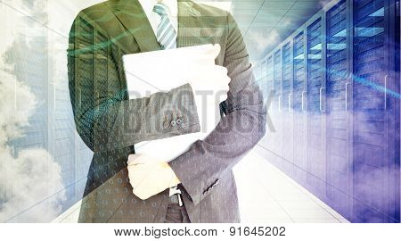 Businessman holding his laptop tightly against digitally generated server room with towers