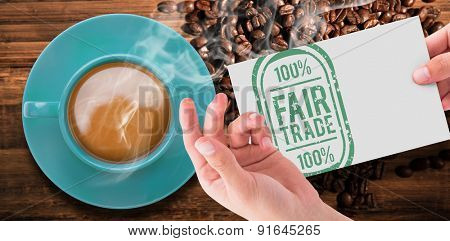 Hand showing card against coffee beans