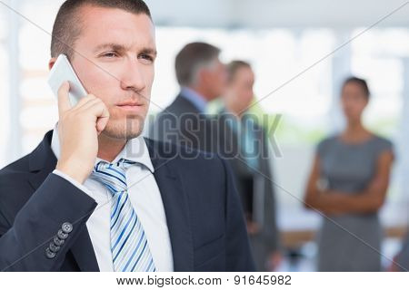 Businessman on the phone with colleagues behind him in the office