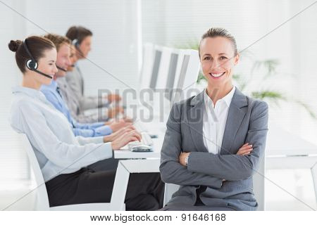 Manager smiling at camera with her staff behind in call center